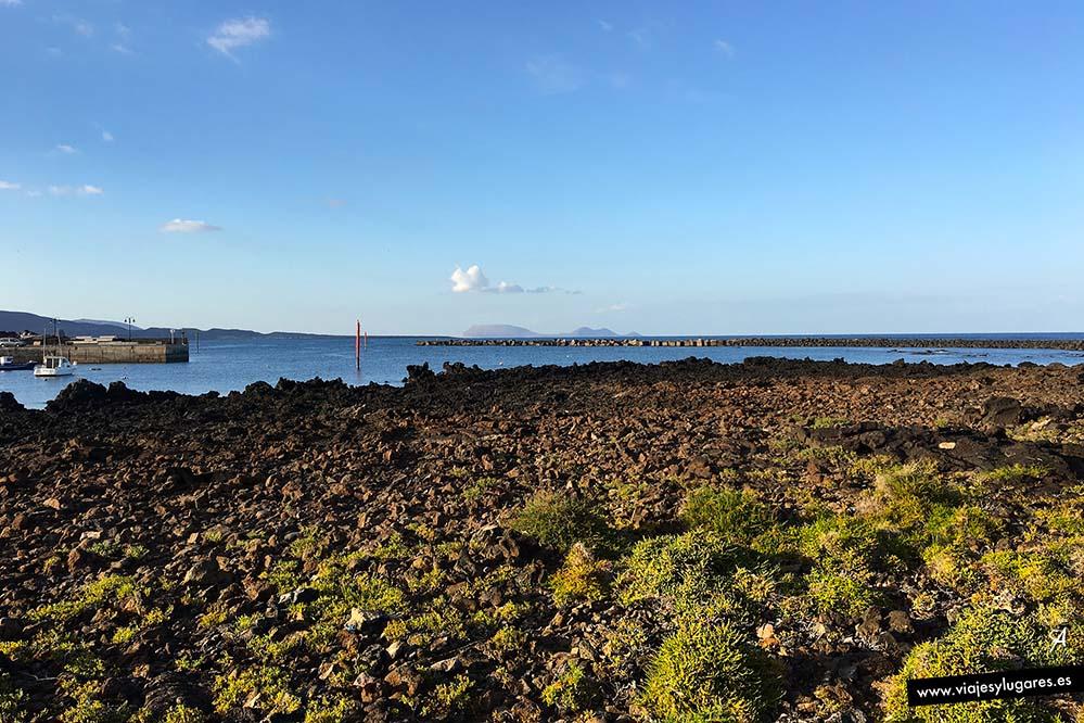 Verde, roca negra volcánica, azul del mar y La Graciosa.